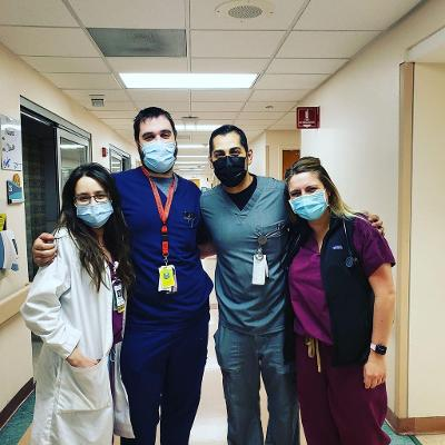 4 people posing together wearing mask in the hall.