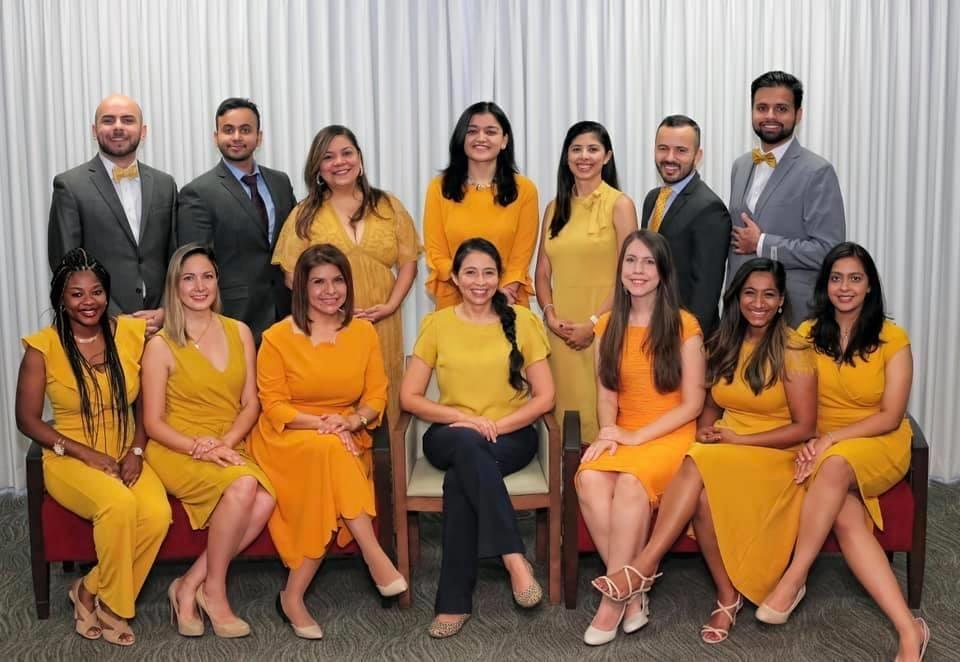 2020 pediatrics team. Dressed in yellow dresses and grey suits. Half are sitting in chairs in front and the rest are standing behind.