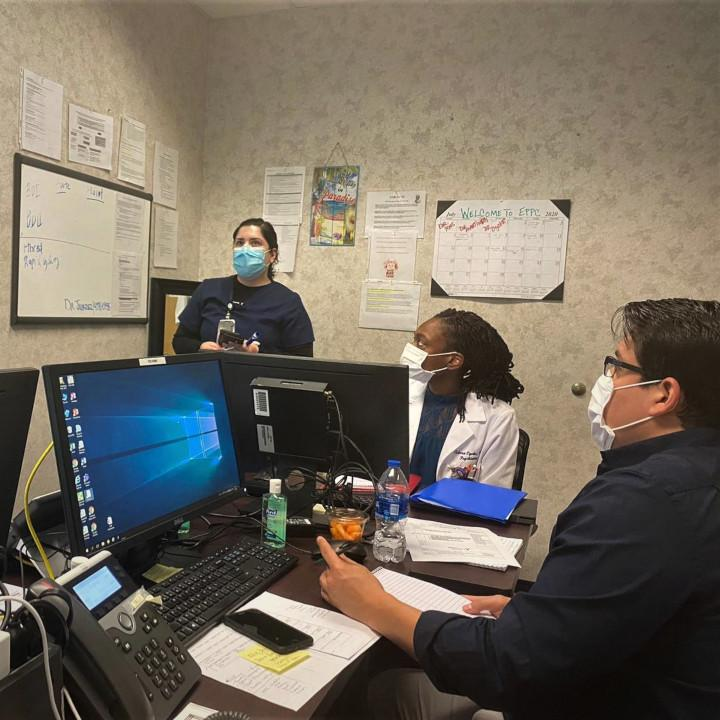 Three faculty with wearing mask in a conference room.