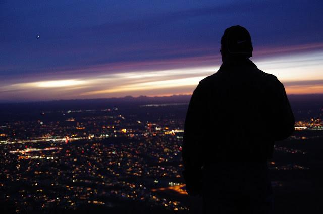 Silhouette of a person at Scenic View El Paso at dusk with a moon in the distance looking over El Paso.