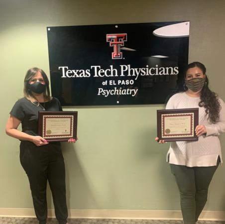 Two psychologist wearing mask and holding certificates.