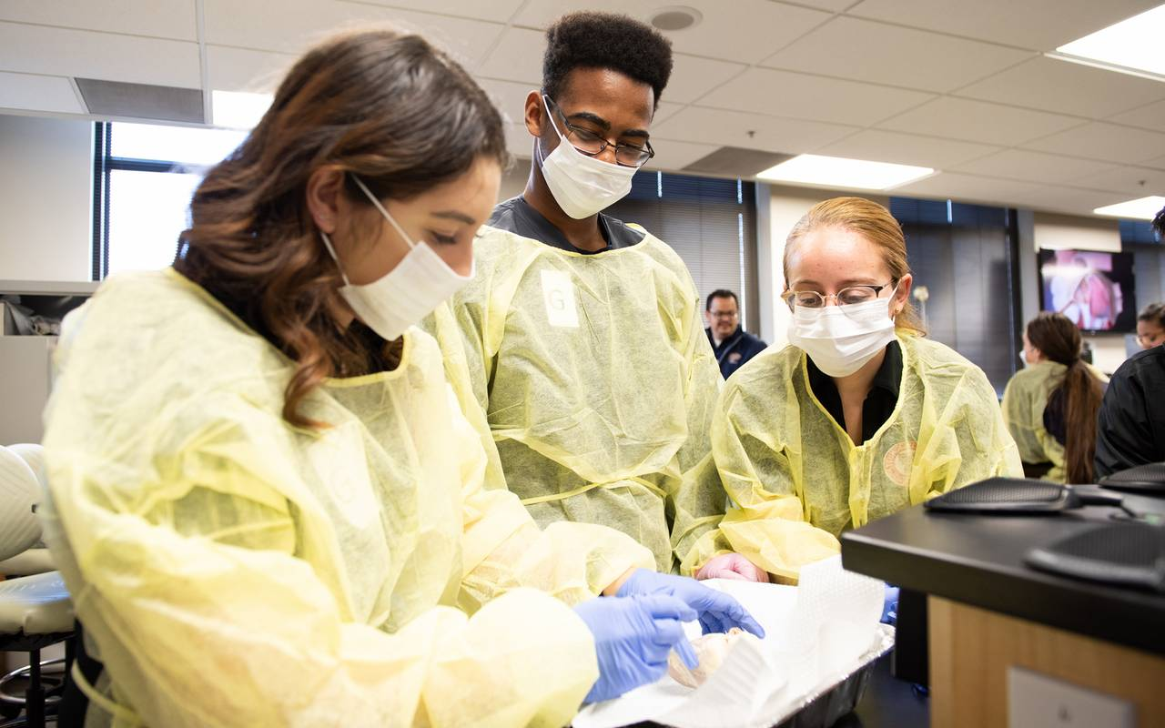 A TTUHSC El Paso student and two middle school students dressed in surgical gowns and masks work on a hands-on project.