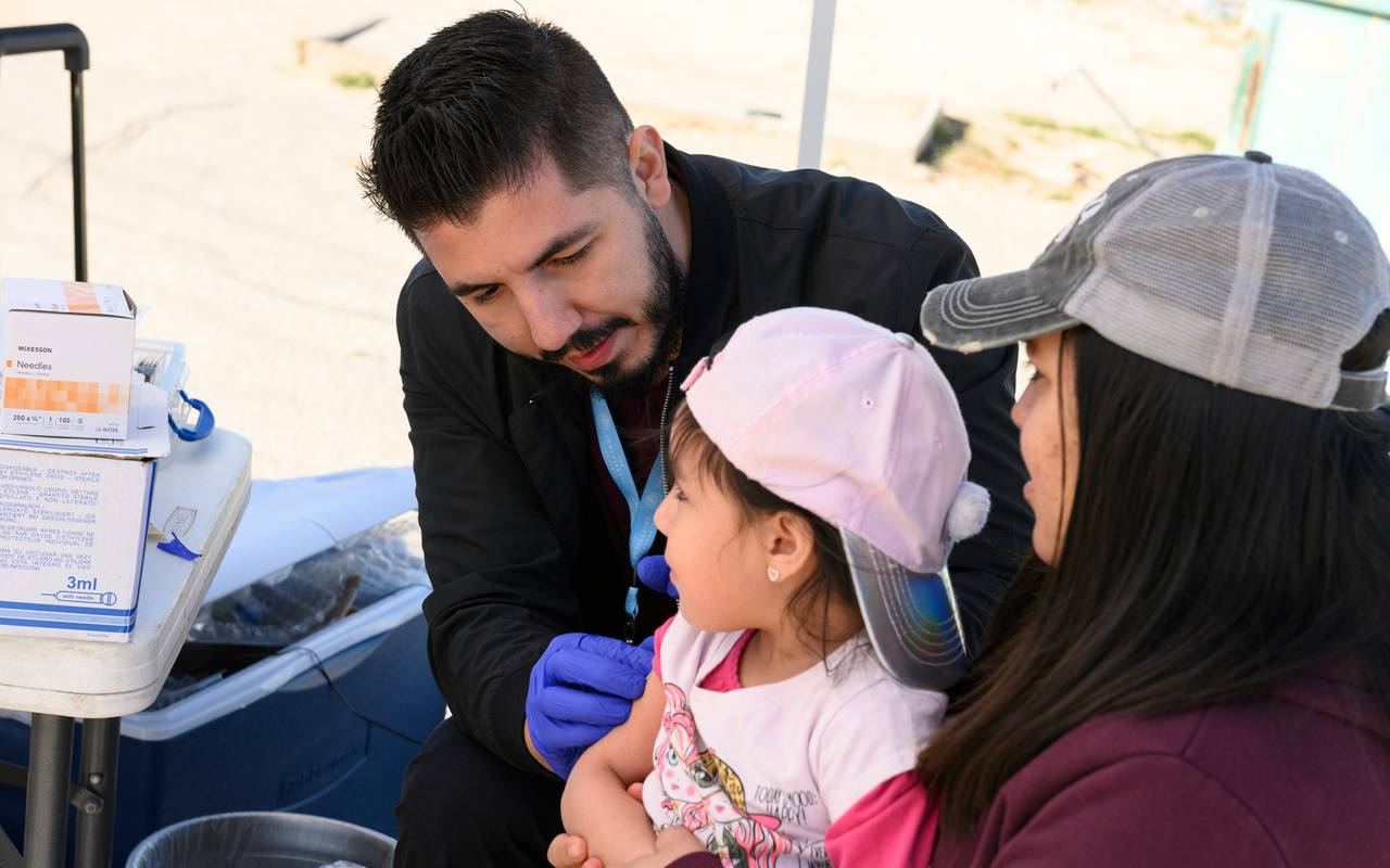A man cares for a child and her mother during an immunization clinic in Sparks.