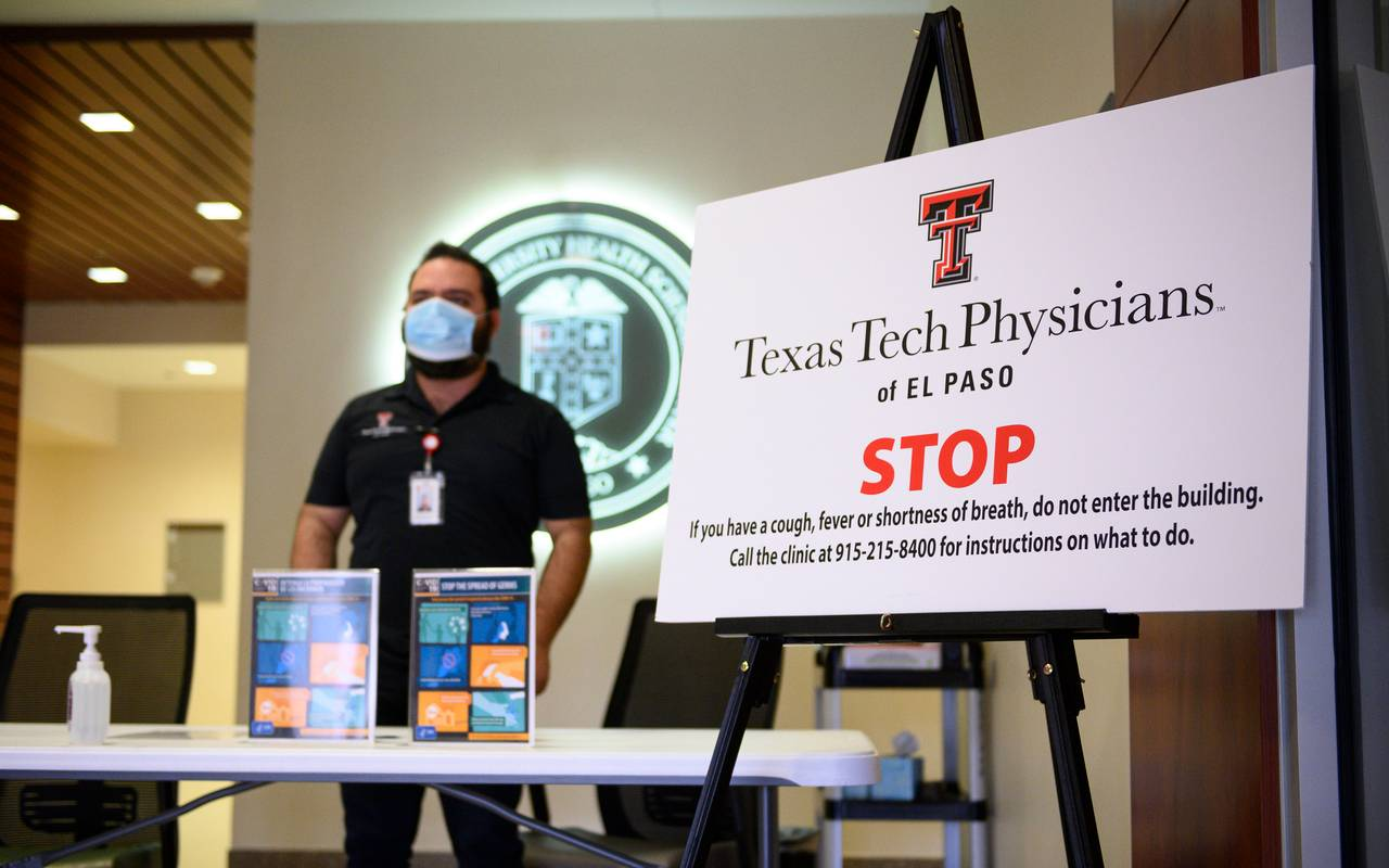 A Texas Tech Physicians of El Paso employee stands at the entrance of a clinic next to a sign with instructions for entering the building.