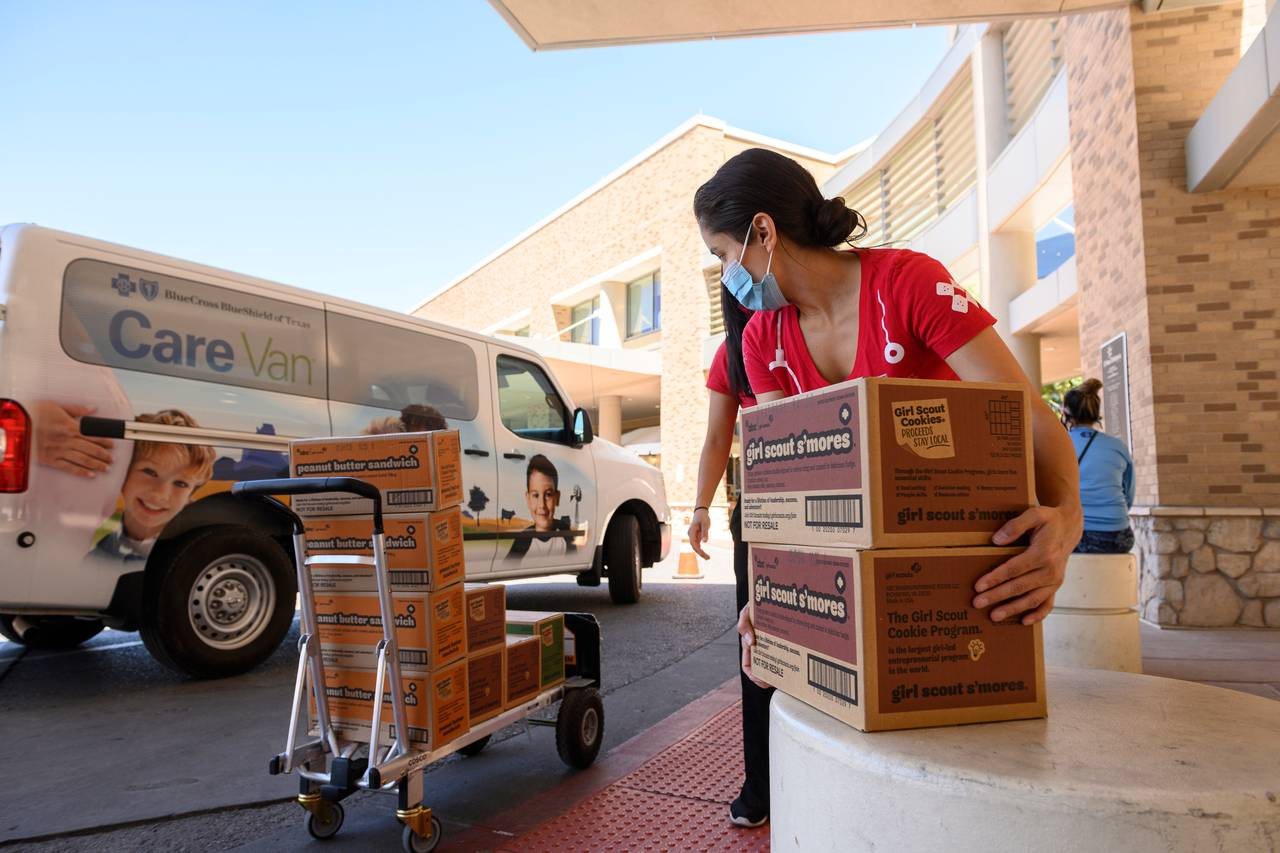 Andrea Tawney, Ph.D., moves boxes of donated Girl Scouts Cookies outside El Paso Children's Hospital.