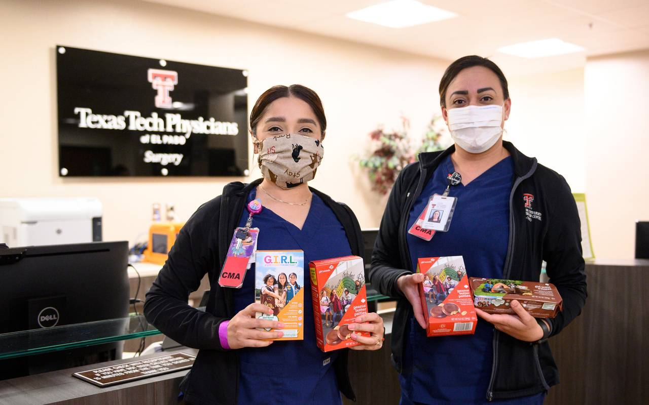 Two nurses hold donated boxes of Girl Scout cookies at a Texas Tech Physicians of El Paso clinic.
