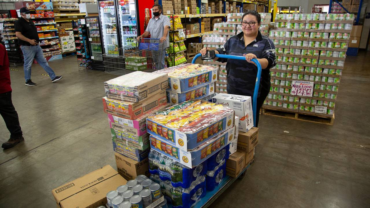A woman stands beside a donated cart of non-perishable food for the RaiderAid food pantry.