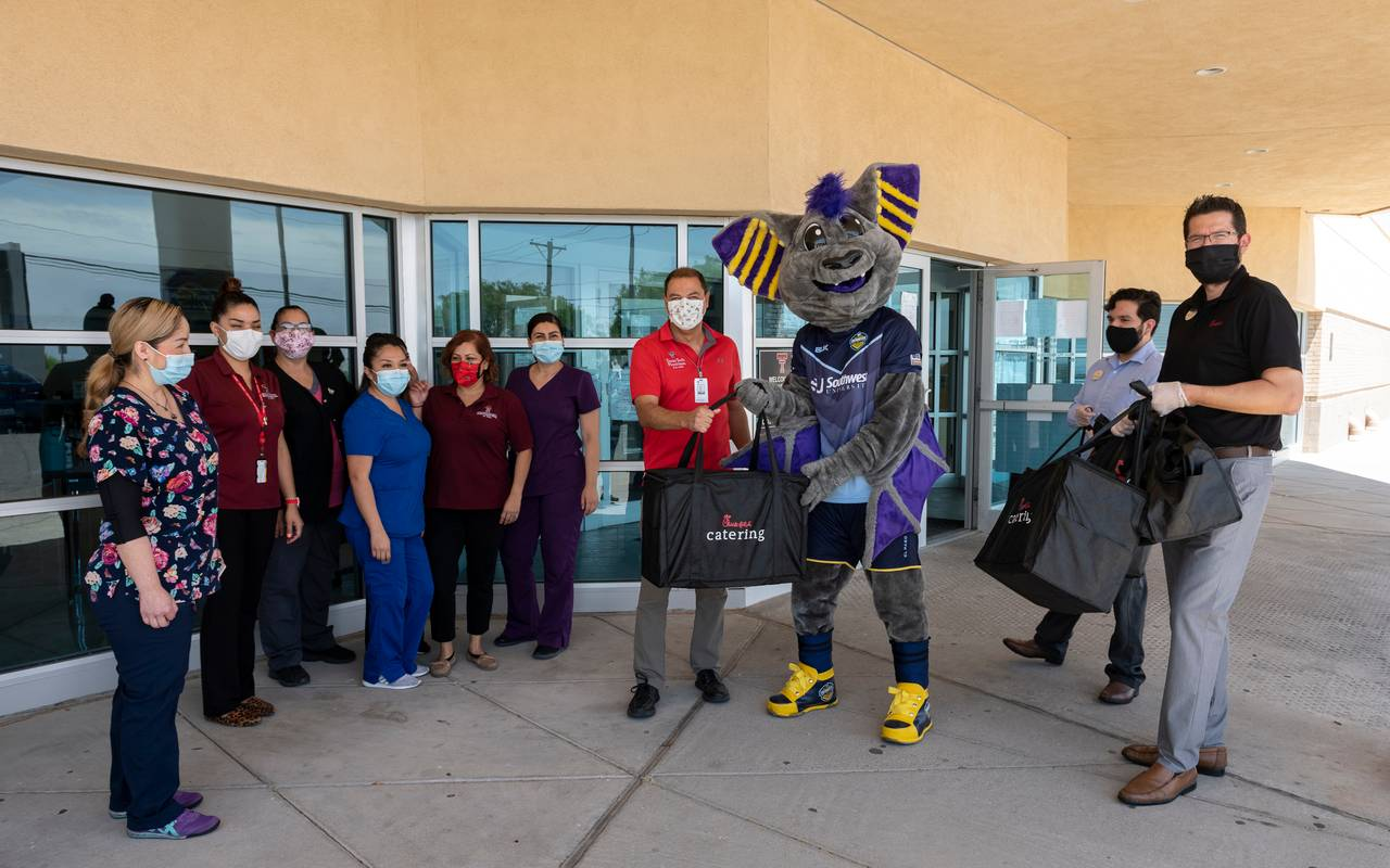 Texas Tech Physicians of El Paso employees with Chick-fil-A officials and the El Paso Locomotive FC mascot, Ozzy the bat, during a meal donation.