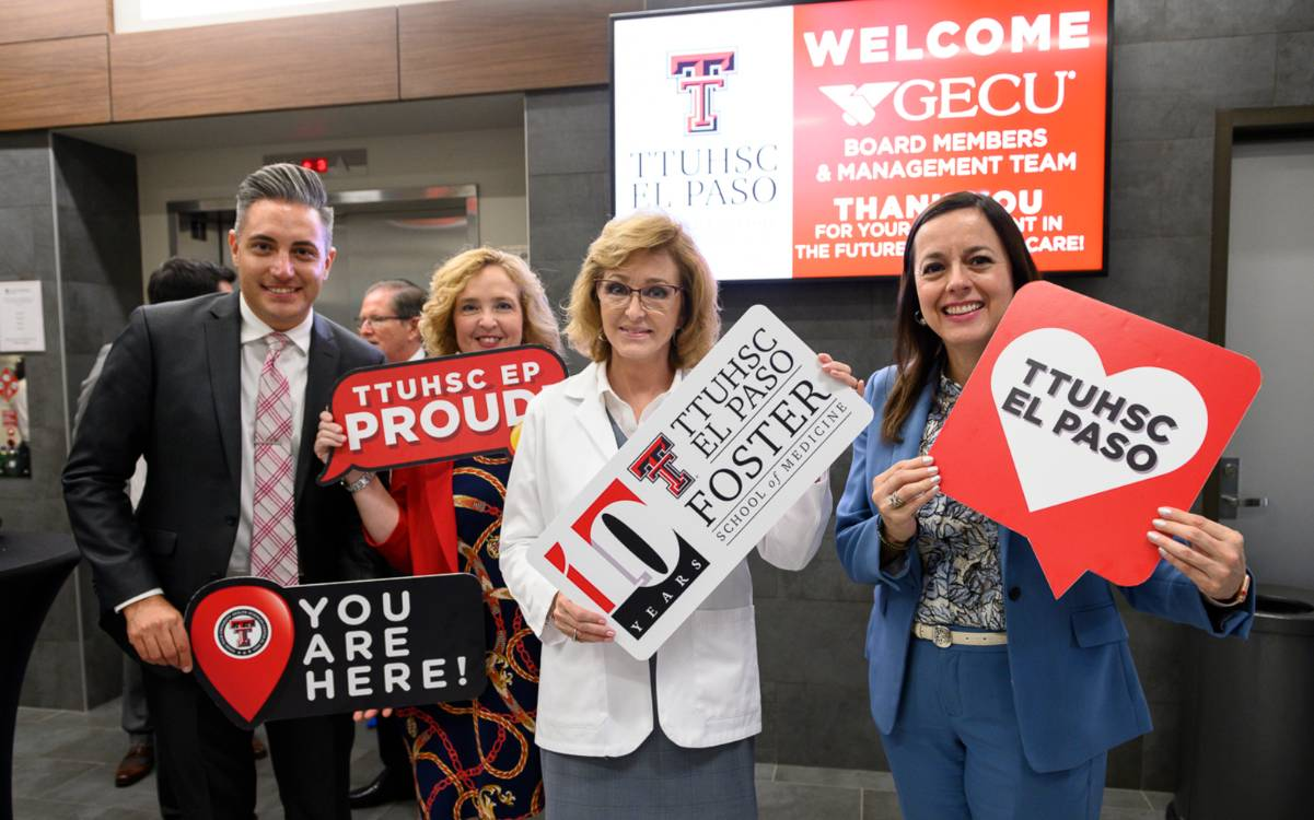 Four community supporters of TTUHSC El Paso hold decorative signs commemorating the Foster School of Medicine's 10-year anniversary.