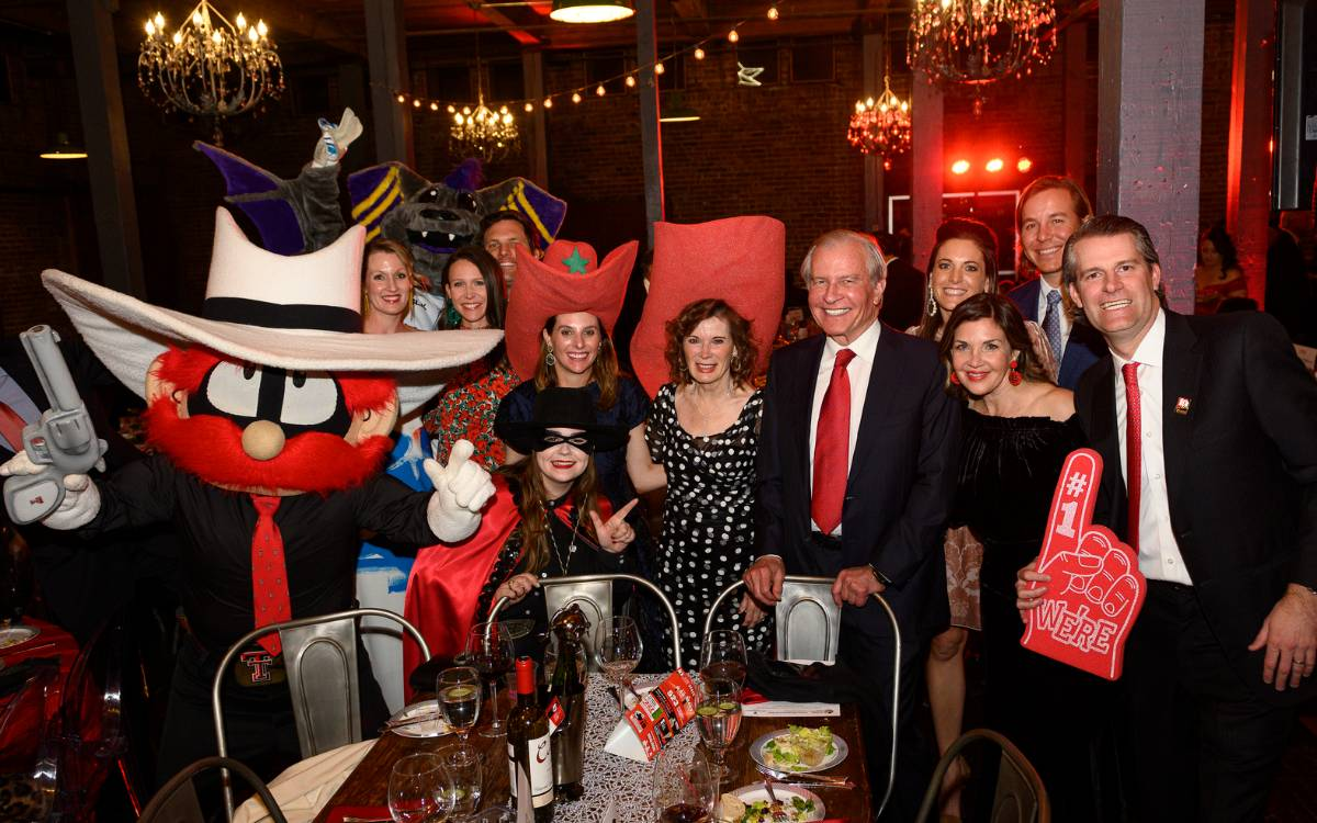 A group of guests at the Hunt Family Foundation table with Texas Tech mascots Raider Red and the Masked Rider.
