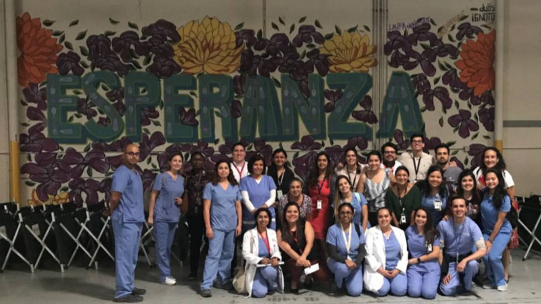 "A group of TTUHSC El Paso residents stand in front of a wall with a mural that says ""Esperanza."""